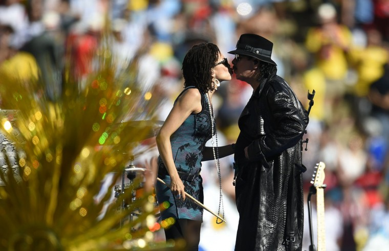 Mexican musician Carlos Santana (R) kisses his drummer as he performs during the closing ceremony prior to the 2014 FIFA World Cup final football match between Germany and Argentina at the Maracana Stadium in Rio de Janeiro, Brazil, on July 13, 2014. (Fabrice Coffrini/AFP/Getty Images)