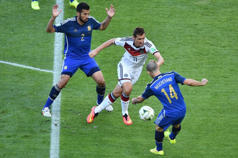 Germany's forward Miroslav Klose (C) tackles Argentina's midfielder Javier Mascherano (R) as Argentina's defender Ezequiel Garay looks on during the final football match between Germany and Argentina for the FIFA World Cup at The Maracana Stadium in Rio de Janeiro on July 13, 2014. (Gabriel Bouys/AFP/Getty Images)