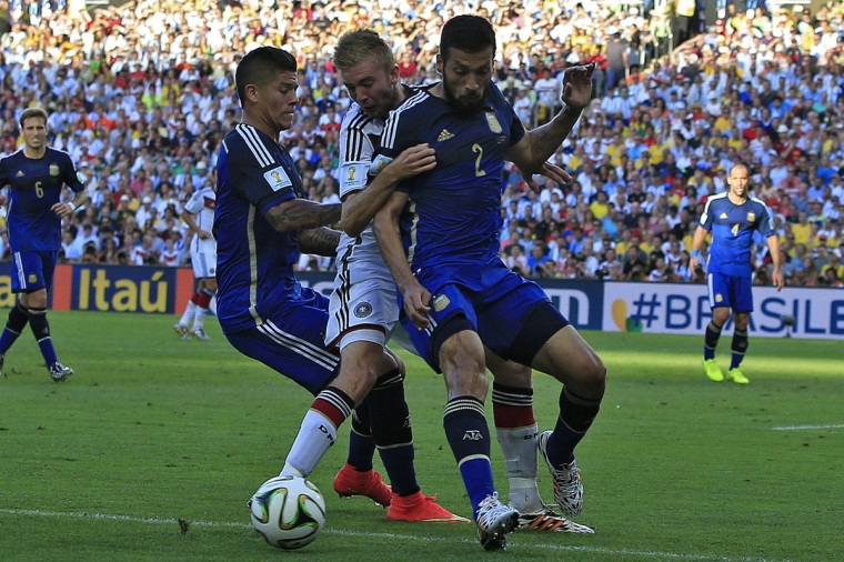 Germany's midfielder Christoph Kramer (C) is challenged by Argentina's midfielder Enzo Perez (L) and Argentina's defender Ezequiel Garay during the 2014 FIFA World Cup final football match between Germany and Argentina at the Maracana Stadium in Rio de Janeiro on July 13, 2014. (Adrian Dennis/AFP/Getty Images)