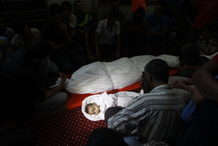 Palestinian mourners gather around the body of five-month-old Fares al-Mahmum and another victim of Israeli bombardment during their funeral on July 18, in Rafah, in the southern Gaza Strip. The Palestinian infant was one of five people killed by Israeli fire in separate incidents in the southern city, as Israel pressed a ground offensive on the 11th day of a massive operation.   || CREDIT: SAID KHATIB - AFP/GETTY IMAGES