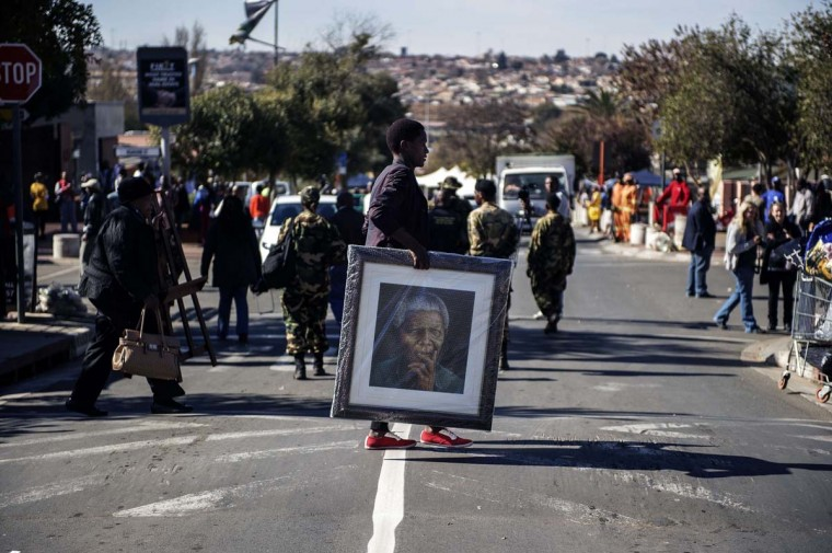 "A woman carries a painting portraying the late Nelson Mandela outisde his former house in Soweto as various activities marking International Mandela Day take place in front of the house turned museum of the late global Icon Nelson Mandela on July 18 in Johannesburg. Mandela Day is a global call to action that celebrates the idea that each individual has the power to transform the world, the ability to make an impact. Two decades after Mr. Mandela's election by the South African parliament, activists in Malta have been fined for their use of a banner reading ""stop Israeli Apartheid"" according to news outlet Malta Today.