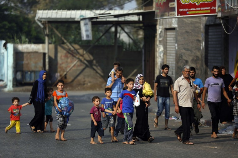 Palestinians flee their homes in Gaza's eastern Shejaiya district on July 20, 2014, after heavy Israeli shelling that left casualties lying in the streets, an AFP correspondent reported. Ambulances were unable to reach much of the area along the border because of heavy fire, and emergency services told AFP there were reports of dead and wounded trapped by the bombardment. (Mohammed Abed/AFP/Getty Images)