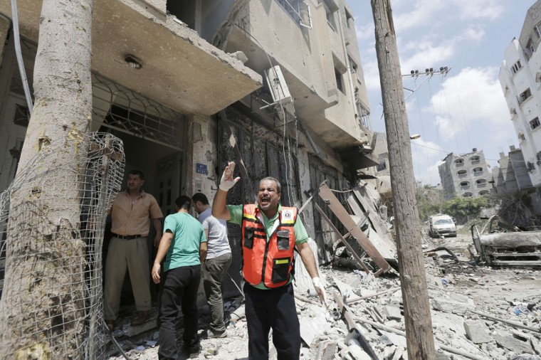"A Civil defence worker shouts during an Israeli military offensive on the Shejaiya neighborhood between Gaza City and the Israeli border, which has left more than 50 people dead in a blistering bombardment which began overnight, medics said on July 20, 2014. The death toll in Gaza passed 400 as Israel pressed its biggest offensive in the enclave in five years, Palestinian health officials said. ""410 people have been killed since the war started and more than 3,020 people have been injured, most of them civilians,"" deputy health minister Yussef Abu Rish told reporters at al-Shifa hospital in Gaza City. (Mohammed Abed/AFP/Getty Images)"