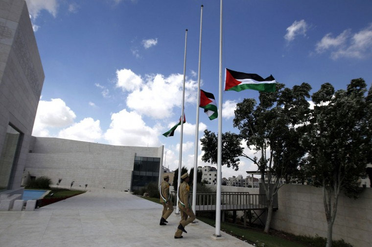 "Palestinians soldiers lower the Palestinian flags to half mast at the Muqataa Compound, on July 20, 2014, in the West Bank city of Ramallah, to show respect for all the people killed in the Gaza Strip during the Israeli military offensive ""Operation Dove"". Palestinian president Mahmud Abbas has called for three days of mourning. (Abbas Momani/AFP/Getty Images)"