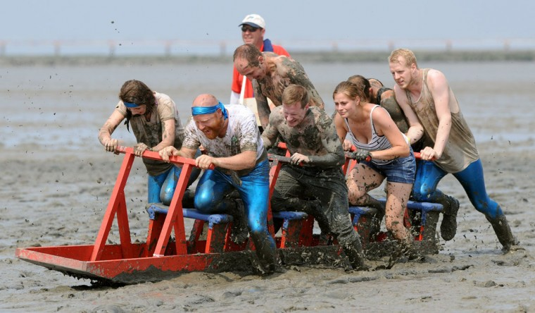"""Participants of the mudflat sledge championships push their sledge through the wadden sea on July 20, 2014 in Upleward, northern Germany. The competition was titled """"Dirty sports for a clean job"""" and was a charity event in favor of a regional association fighting against cancer. (Ingo Wagner/AFP/Getty Images)"""