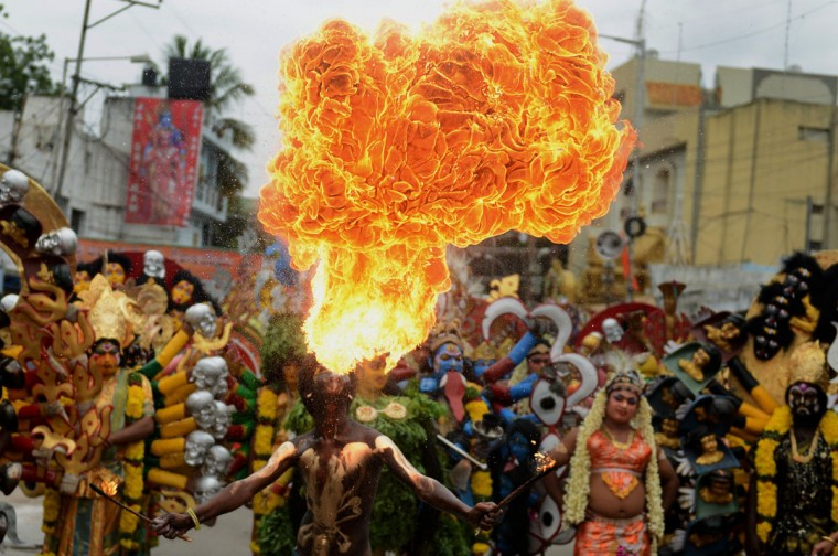 An Indian artist performs during the final procession of the eleven-day traditional festival of 'Bonalu', a ritual offering to the goddess MahaKali, at Sri Akkanna Madanna Mahankali Temple in Hyderabad on July, 21 2014. The Goddess is honoured mostly by women during Bonalu festival with offerings of food and dancing. (AFP PHOTO/Getty Images/Noah Seelam)