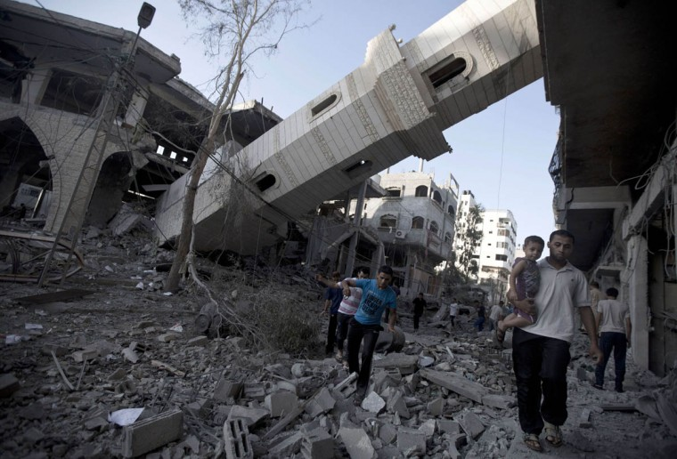 "Palestinians walk past the collapsed minaret of a destroyed mosque in Gaza City, on July 30 2014 after it was hit in an overnight Israeli strike. Overnight Israeli bombardments killed ""dozens"" of Palestinians in Gaza, including at least 16 at a UN school, medics said, on day 23 of the Israel-Hamas conflict. (Mahmud Hams/Getty Images)"