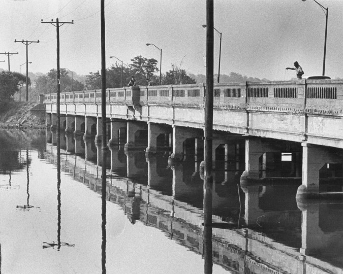 No matter how early in the day at least a few anglers can be spotted on the Hanover street bridge. Telephone poles and bridge piers form a pattern under them. (Lloyd Pearson, June 9, 1969, Sun photo)