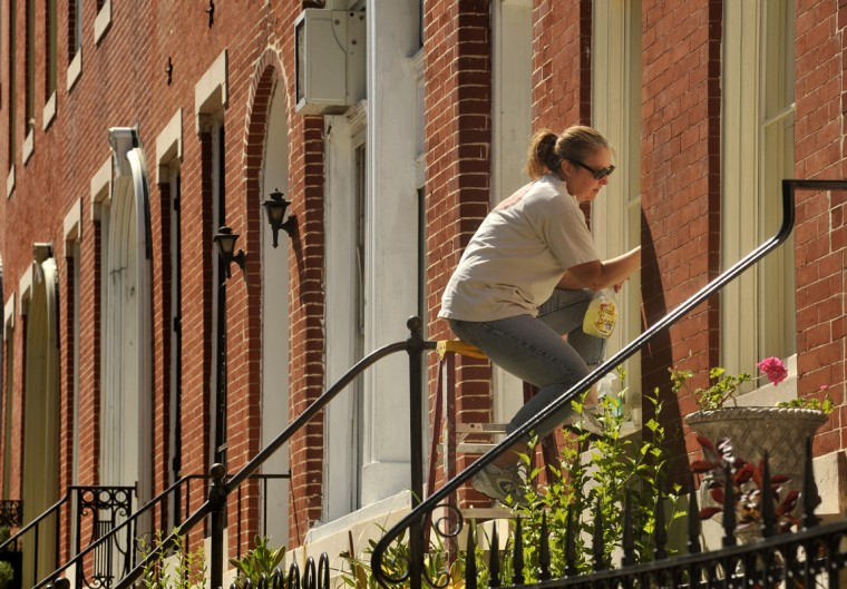 Mary Ernish took advantage of the pleasant sunny weather to scrape excess paint after stripping and repainting the window frames on her Hollins Street rowhouse in Union Square. She and her husband are using Maryland Historic Trust tax credits for the restoration of their 1886 Italianate rowhouse to its original appearance. (Amy Davis/Baltimore Sun/May 2010)