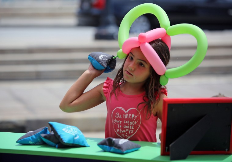 Emma Miniane, 7, takes aim at the Black Hole Cornhole, one of the five games at Supergame!, an interactive art installation designed by Baltimore-based artists Scott Pennington and Adam Franchino. (Al Drago/Baltimore Sun)