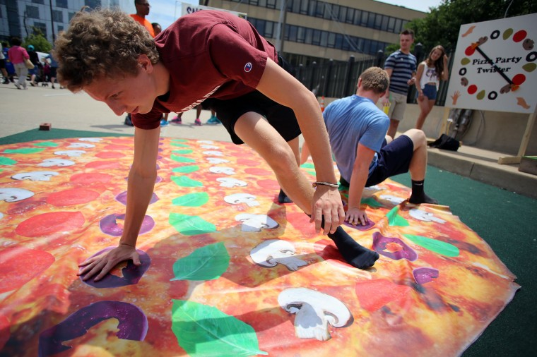 Caleb Arisman, from Baltimore, reaches around as he puts his left foot on pepperoni as he plays Pizza Party Twister with his friend Caleb Smith at ArtScape 2014. Arisman's friends Emily Middleton and Tyler Hands spun the wheel as they directed the Caleb's where to move. (Al Drago/Baltimore Sun)