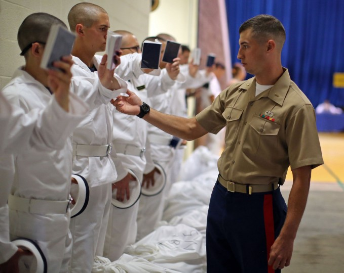 Plebes have the angle of their arms adjusted as they study their reef points, which contain basic information on how to act as a midshipmen during Induction Day at the U.S. Naval Academy. (Al Drago/Baltimore Sun)