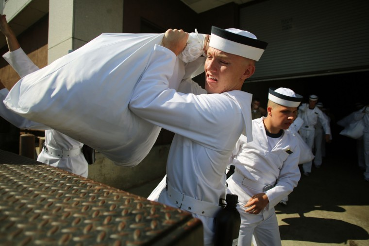 A plebe loads his belongings onto a truck as he leaves check-in to head to his barracks during Induction Day. (Al Drago/Baltimore Sun)
