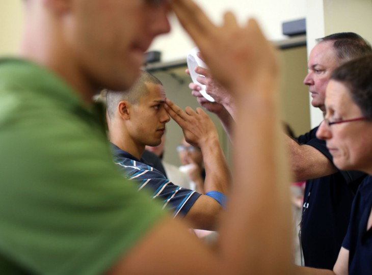 Daniel Iskandar, center, from Madison, New Jersey, has his cap fitted to a size 7 by Richard Gates, from the midshipman's store during Induction Day. (Al Drago/Baltimore Sun)