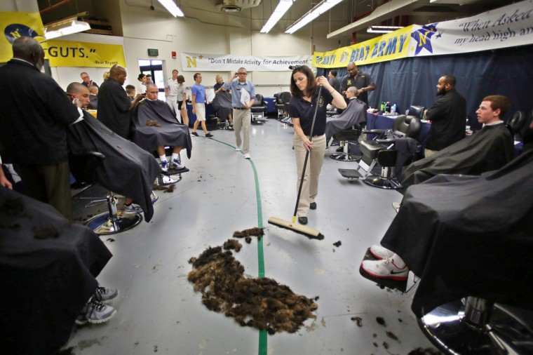 Administrative assistant Amanda Guinn sweeps up hair shaved off of almost 1,200 prospective plebes during Induction Day at the U.S. Naval Academy. (Al Drago/Baltimore Sun)