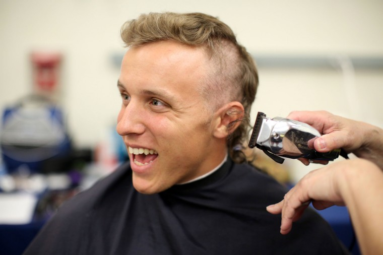 Benjamin McGrath, from West Palm Beach Florida, laughs as his head is shaved by Louise Gregory during Induction Day at the U.S. Naval Academy. (Al Drago/Baltimore Sun)