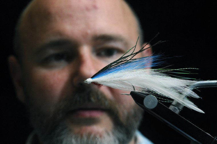 Theaux Le Gardeur of Backwater Angler in Monkton ties a Lefty Deceiver using fly tying materials that include bird feathers, deer fur, threads, and synthetic dubbing on a hook. (Kenneth K. Lam/Baltimore Sun)