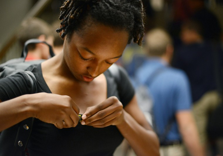Plebe Aaliyah Gordon puts on her name tag in Alumni Hall for Induction Day. (Rachel Woolf/Baltimore Sun)