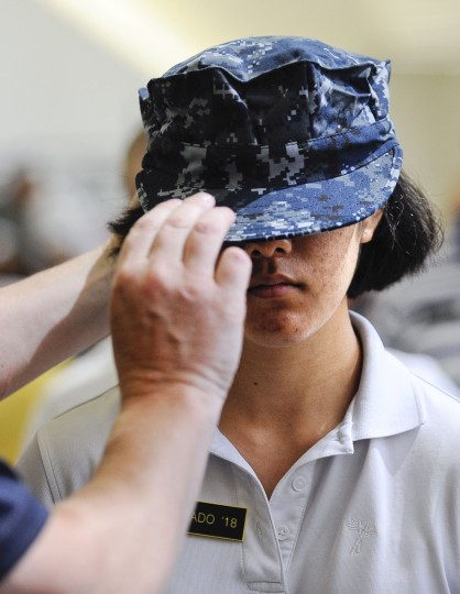 Plebe Amanda Alvarado, of California, has her hat fitted by Dave Klose in Alumni Hall for Induction Day. (Rachel Woolf/Baltimore Sun)