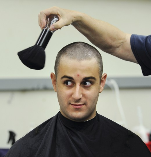 Plebe Kyle Festa, of Virginia, has his freshly shaved head brushed by Louise Gregory in Alumni Hall for Induction Day Tuesday morning. (Rachel Woolf/Baltimore Sun)