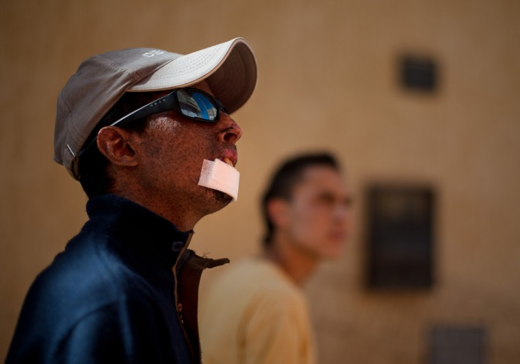 From left, Driss Hamouti, 21, of Tifelt, Morocco, looks up into the sun during an early evening walk with his best friend, Zahir Bouten, 21. Hamouti wears a hat and his protective sunglasses while in the sun, but continues to go outside, even without reapplying sunscreen or wearing a more protective garment. Rachel Woolf/Baltimore Sun