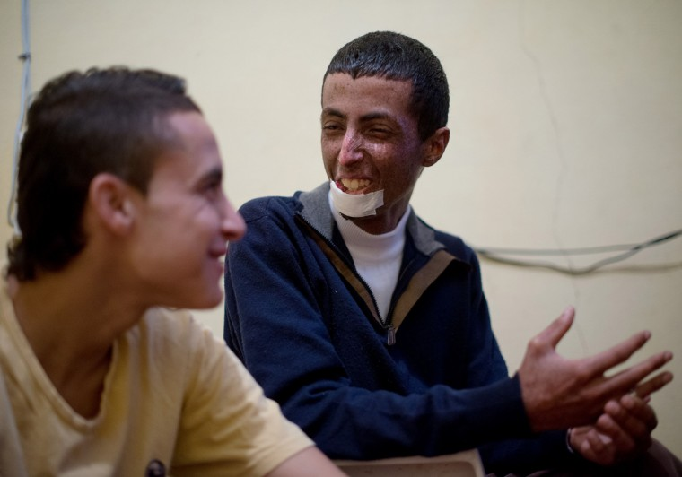 From left, Zahir Bouten, 21, laughs with Driss Hamouti, 21, both of Tifelt, Morocco, during a soccer video game. Bouten and Hamouti have been best friends for 12 years. Rachel Woolf/Baltimore Sun
