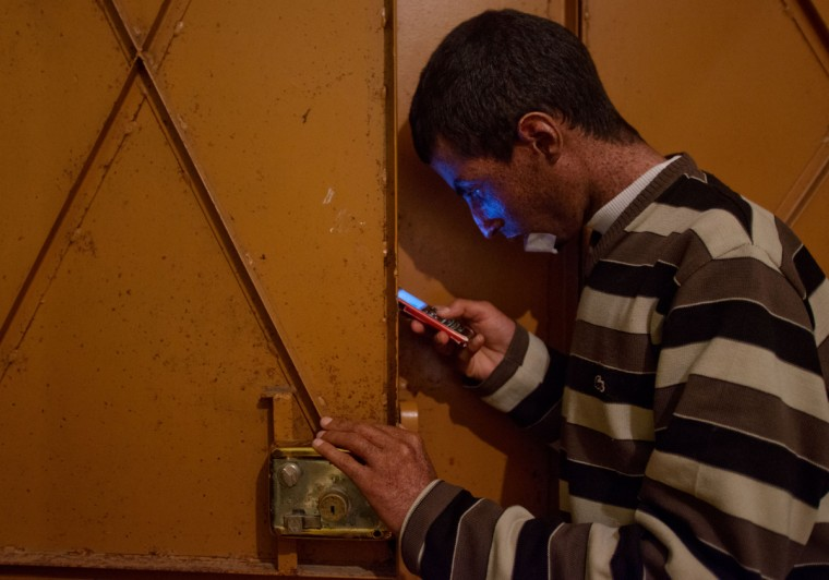Driss Hamouti, 21, of Tifelt, Morocco, glances at his phone next to the door in his room. While Driss spends time in his room, he opens the door but sits in the shade, sometimes to let air in the room. Rachel Woolf/Baltimore Sun