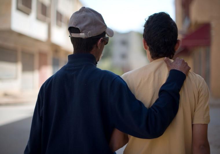 """From left, Driss Hamouti, 21, puts his arm around his best friend, Zahir Bouten, 21, both of Tifelt, Morocco, as they take a walk around Tifelt. """"If he has somewhere to go, he will go. He doesn't care,"""" said Driss' sister, Wafae Hamouti, (not pictured). Rachel Woolf/Baltimore Sun"""
