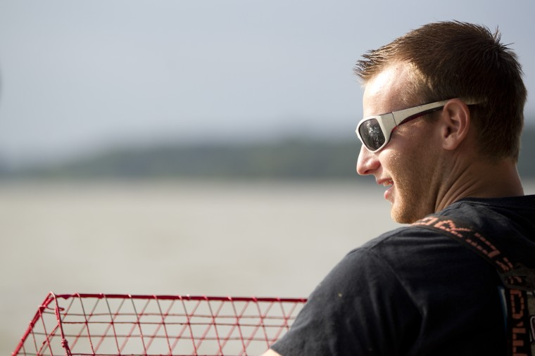Deckhand Tommy Davis, 25, of Kingsville pulls in a crab pot while crabbing on Tony Conrad's boat. (Jen Rynda)
