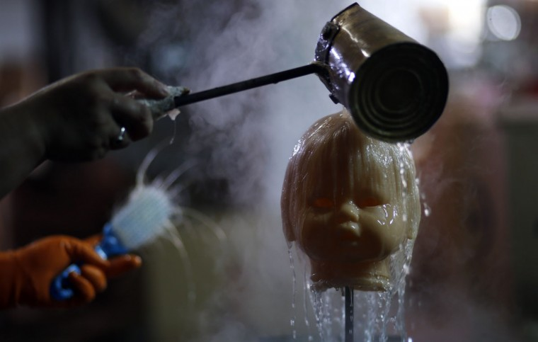 An employee pours water over a doll's head before brushing its hair inside the toy factory owned by Norberto Garcia in Buenos Aires, July 28, 2014. Garcia was poised to launch a series of new toys this year after grafting hard for the past decade to rebuild his business following Argentina's 2001-2002 economic crash and debt default. Instead, he's hunkering down for a possible second default this Thursday, cutting investment plans and scaling back his targets. (REUTERS/Marcos Brindicci)