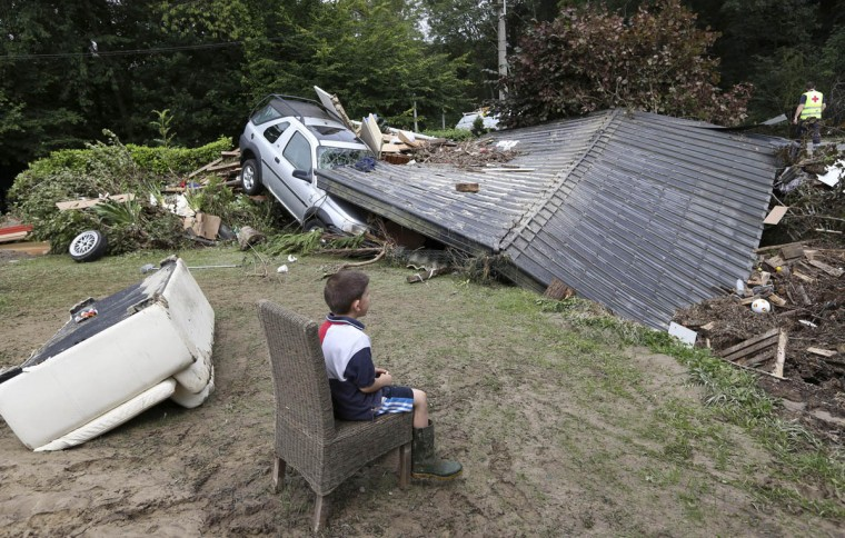 A boy sits near a car stuck under a roof, which collapsed after heavy rains and floods hit the town of Ittre July 30, 2014. (Francois Lenoir/Reuters photo)