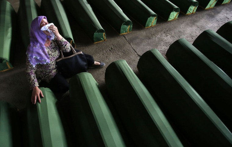 A Bosnian Muslim woman cries near coffin of a relative, which is one of the 175 coffins of newly identified victims from the 1995 Srebrenica massacre, in Potocari Memorial Center, near Srebrenica, July 10, 2014. Family members, foreign dignitaries and guests are expected to attend a ceremony in Srebrenica on July 11, marking the 19th anniversary of the massacre in which Bosnian Serb forces commanded by Ratko Mladic killed up to 8,000 Muslim men and boys. The remains of 175 identified victims will be buried at a memorial cemetery during the ceremony. Their bodies were found in some 60 mass graves around the town. REUTERS/Dado Ruvic