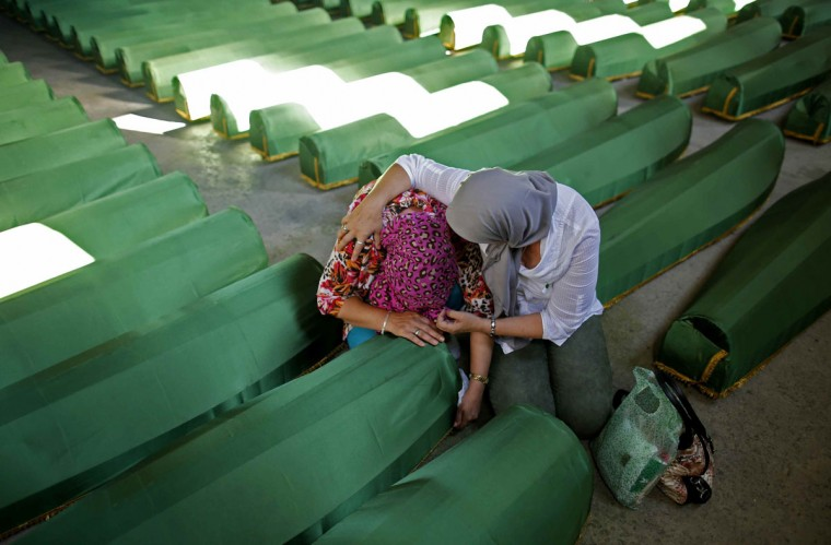 Bosnian women cry near a coffin of their relative, one of the 173 coffins of newly identified victims from the 1995 Srebrenica massacre, in the Potocari Memorial Center, near Srebrenica, July 9, 2014 . Family members, foreign dignitaries and guests are expected to attend a ceremony in Srebrenica on July 11, marking the 19th anniversary of the massacre in which Bosnian Serb forces commanded by Ratko Mladic killed up to 8,000 Muslim men and boys. The remains of 173 identified victims will be buried at a memorial cemetery during the ceremony. Their bodies were found in some 60 mass graves around the town. REUTERS/Dado Ruvic