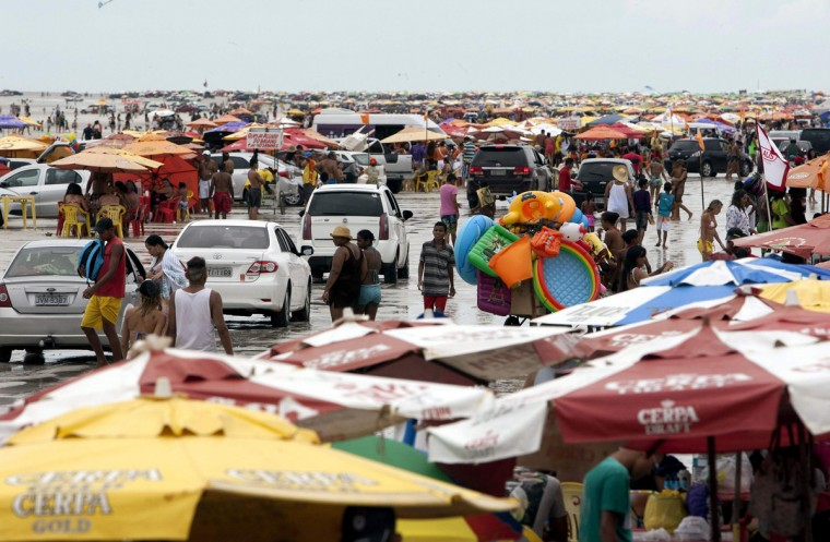 Beachgoers walk next to vehicles during the peak of the summer vacation season on Atalaia beach in Salinopolis, Para state, July 27, 2014. Salinopolis, with a population of 40,000, receives an estimated 280,000 visitors during the month of July, mostly to enjoy the beaches located just southeast of the Amazon river's mouth where the river's fresh water mixes with the Atlantic Ocean's salt water, tourism officials said. Officials estimate that close to 50,000 vehicles drive onto the city's two most popular beaches, Atalaia and Farol Velho, with tons of garbage left by visitors. Picture taken July 27, 2014. REUTERS/Paulo Santos