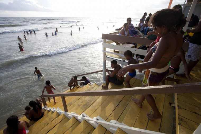 Tourists spend time in a beachside kiosk as others play in the water during the peak of the summer vacation season on Atalaia beach in Salinopolis, Para state, July 27, 2014. Salinopolis, with a population of 40,000, receives an estimated 280,000 visitors during the month of July, mostly to enjoy the beaches located just southeast of the Amazon river's mouth where the river's fresh water mixes with the Atlantic Ocean's salt water, tourism officials said. Officials estimate that close to 50,000 vehicles drive onto the city's two most popular beaches, Atalaia and Farol Velho, with tons of garbage left by visitors. Picture taken July 27, 2014. REUTERS/Paulo Santos