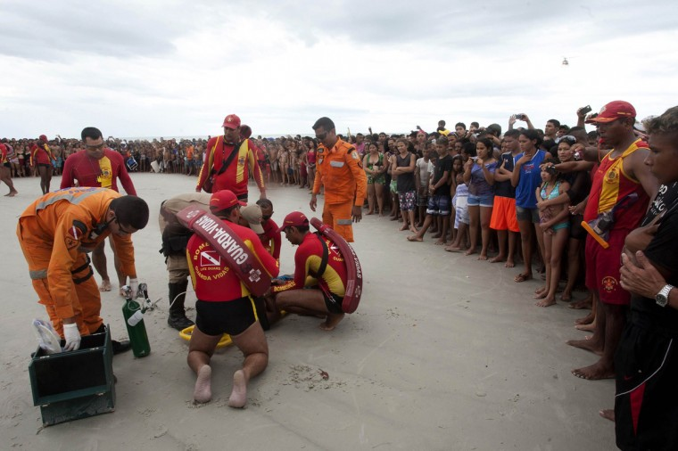 Beachgoers watch what they thought was a real rescue of a drowning victim before learning it was just a practice drill by firemen and lifeguards, during the peak of the summer vacation season on Atalaia beach in Salinopolis, Para state, July 27, 2014. REUTERS/Paulo Santos