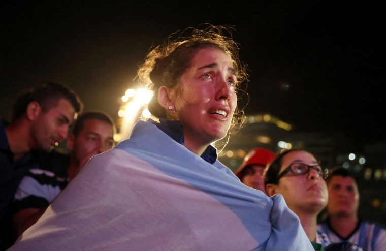 An Argentine fan cries as she watches Argentina's defeat to Germany in their 2014 World Cup final match, on Copacabana beach in Rio de Janeiro July 13, 2014. (Pilar Olivares/Reuters)
