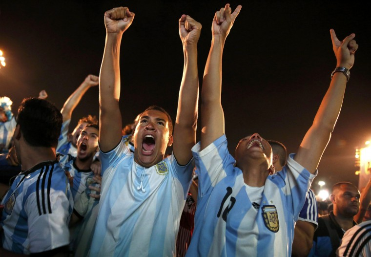 Argentinian soccer fans react during the penalty shootout as they watch a broadcast of the 2014 World Cup semi-final against the Netherlands at Copacabana beach in Rio de Janeiro, July 9, 2014. (Pilar Olivares/Reuters)