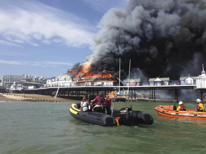 Fire and smoke engulf part of the pier in Eastbourne, southern England July 30, 2014. A Victorian-era seaside pier at Eastbourne on Britain's south coast was badly damaged when fire broke out in an amusement arcade on Wednesday. Flames could be seen leaping from the roof of the two-storey structure and East Sussex Fire and Rescue Service said a large plume of smoke was rising above the town. No injuries were reported. (Benjamin Hall/Reuters photo)