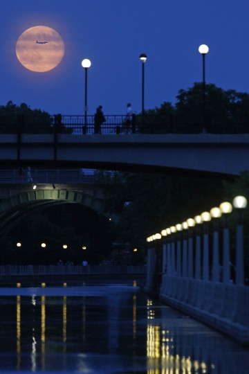 Aircraft passes in front of a Supermoon rising over the Rideau Canal in Ottawa July 12, 2014. Occurring when a full moon or new moon coincides with the closest approach the moon makes to the Earth, the Supermoon results in a larger-than-usual appearance of the lunar disk. REUTERS/Blair Gable