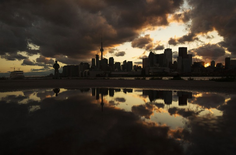 A man stands in front of the skyline after a rainy day in Toronto, July 8, 2014. REUTERS/Mark Blinch
