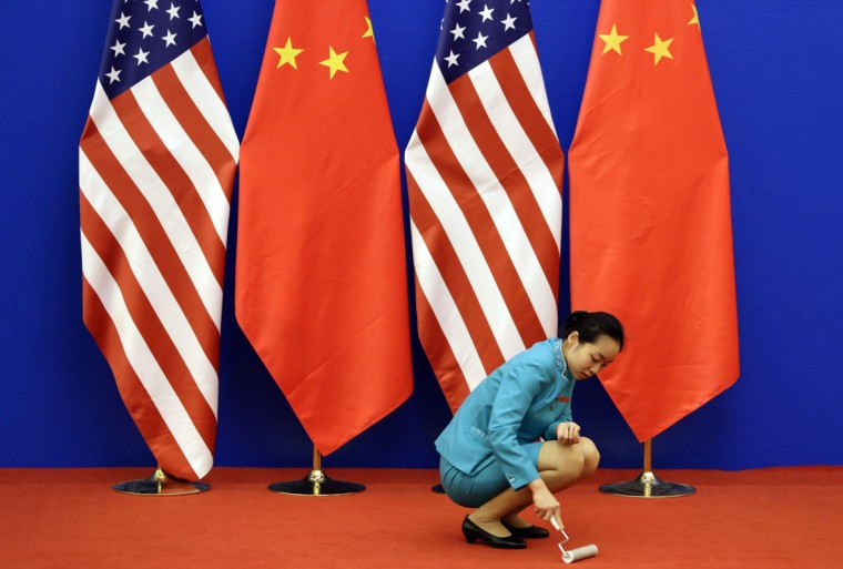 An attendent cleans the carpet next to U.S. and Chinese national flags before a news conference for the 6th round of U.S.-China Strategic and Economic Dialogue at the Great Hall of the People in Beijing, July 10, 2014. REUTERS/Jason Lee