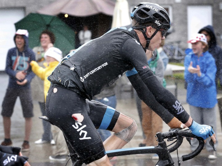 Team Sky rider Christopher Froome of Britain rides in his torn cycling costume after falling in the 5th stage of the Tour de France cycle race between Ypres in Belgium and Arenberg Porte du Hainaut in France, July 9, 2014. Froome's bandaged left knee was from another fall in yesterday's stage. (Christian Hartmann/Reuters)