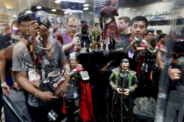 Comic fans look at character dolls from Thor during the 2014 Comic-Con International Convention in San Diego, California July 24, 2014. (Sandy Huffaker/Reuters)