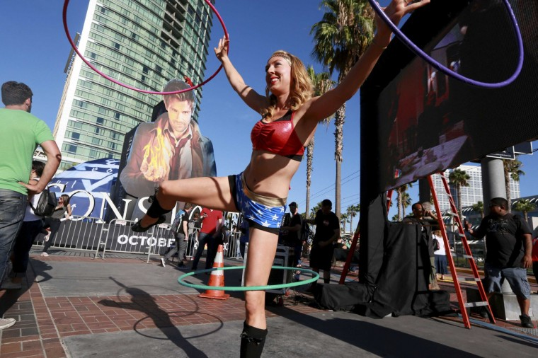 A staff member dressed as Wonderwoman, who gave her name as Hillary Hula, performs at the Gaslamp Quarter in Downtown San Diego during the 2014 Comic-Con International Convention in San Diego, California July 23, 2014. (Sandy Huffaker/Reuters)