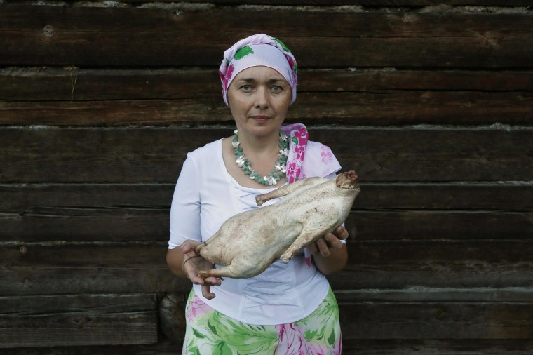 Zelfira Mansurova, a Tatar woman, holds a jerked goose as she poses for a photograph near her house in Russia's Siberian city of Krasnoyarsk, July 10, 2014. During Ramadan, the ninth and holiest month in the Islamic calendar, Muslims refrain from eating and drinking during daylight hours. Reuters photographers took a series of portraits of Muslims observing Ramadan in different countries around the world, and asked them what food they liked to eat when breaking their daytime fast. Eid-al-Fitr, marking the end of Ramadan, will be celebrated at the beginning of next week. Picture taken July 10, 2014. (Ilya Naymushin/Reuters)
