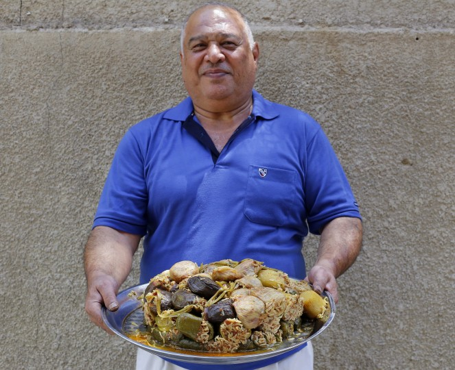 Hussain Hawi Warid, 55, holds a tray of dolma, a traditional Iraqi meal of vegetables and vine leaves stuffed with meat, rice and tomatoes, as he poses for a photograph in Baghdad, July 7, 2014. During Ramadan, the ninth and holiest month in the Islamic calendar, Muslims refrain from eating and drinking during daylight hours. Reuters photographers took a series of portraits of Muslims observing Ramadan in different countries around the world, and asked them what food they liked to eat when breaking their daily fast. Eid-al-Fitr, marking the end of Ramadan, will be celebrated at the beginning of next week. Picture taken July 7, 2014. Ahmed Saad/Reuters)
