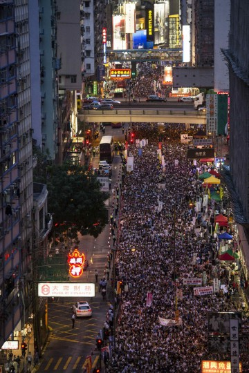 Thousands of pro-democracy protesters gather to march in the streets to demand universal suffrage in Hong Kong July 1, 2014. As tens of thousands gathered in Hong Kong on Tuesday to demand greater democracy and freedom from Beijing's control, China's military garrison stationed in the freewheeling capitalist hub launched its own offensive - to charm them. (REUTERS/Tyrone Siu)