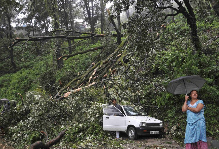 A woman (R) stands near a car which was damaged by a tree that fell after heavy rains and strong winds in the northern Indian hill town of Shimla. Monsoon rains have revived in central and northern parts of India known for soybean and sugarcane cultivation, a government official said on Wednesday, but warned the country is still expected to have below-average monsoon this year. (Reuters)