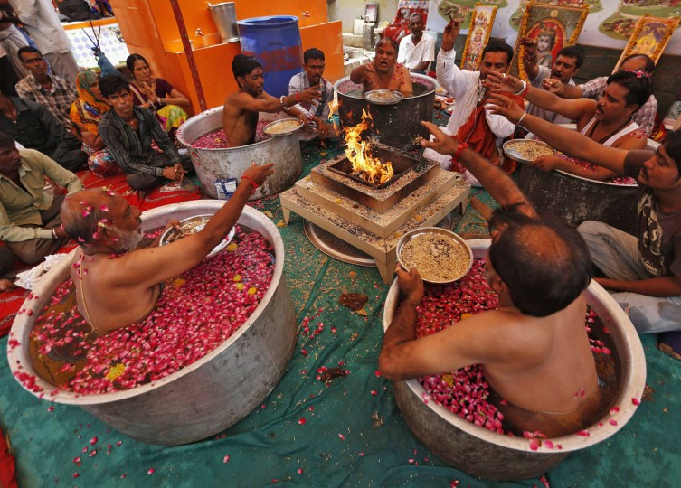 "Hindu priests sit in cauldrons of water and make offerings to in front of a fire while performing the ""Parjanya Varun Yagam"", a special prayer for rain, in the western Indian city of Ahmedabad July 1, 2014. India's monsoon rainfall was 43 percent below average in June, the weather office said on Monday, the weakest first month of the season in five years. REUTERS/Amit Dave)"